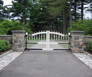 White wooden entry gate with black strap hinges by Tri State Gate, New York