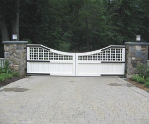 Updated design trellis and solid panel wooden driveway gate by Tri State Gate, New York