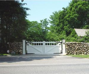 Updated farmhouse design wooden driveway gate by Tri State Gate, New York