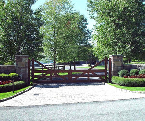 Modern ranch-style wooden driveway gate design by Tri State Gate, New York