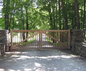 Natural cedar wood gate with vertical posts and wooden cross beam by Tri State Gate, New York
