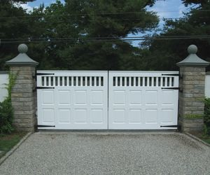 Paneled, composite automatic driveway gate with brick pillars by Tri State Gate, New York