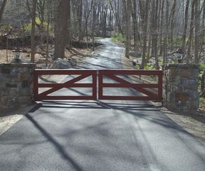 Minimalist farm-style wooden driveway gate with deep mahogany stain by Tri State Gate, New York