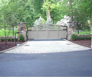 Tan painted composite driveway gate, custom stone pillars by Tri State Gate, New York