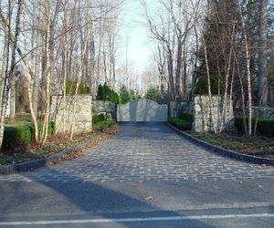 Automated composite driveway gate with stone vestibule by Tri State Gate, New York