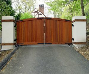 Cedar wood driveway gate with iron stud detail by Tri State Gate, New York