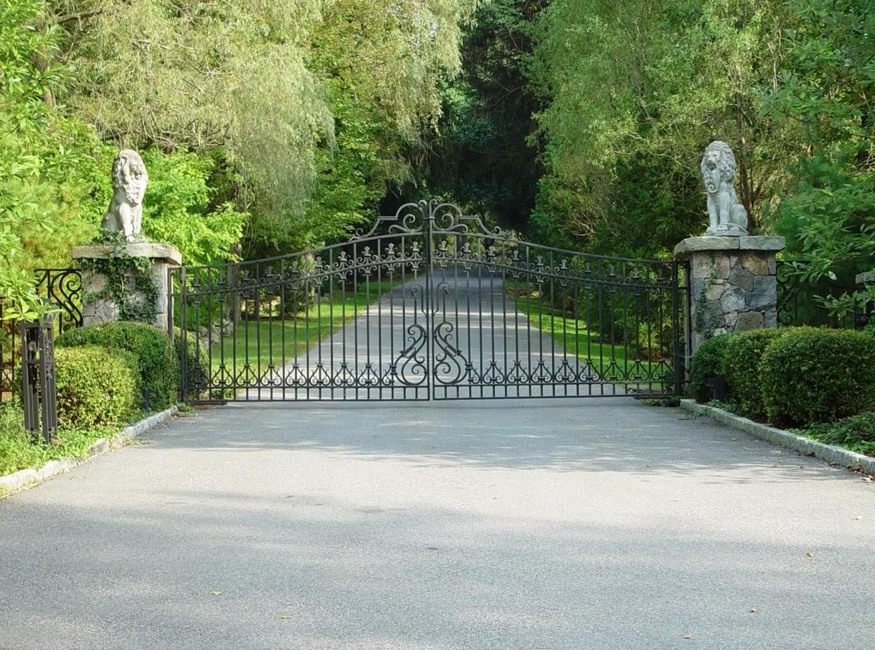 Wrought iron driveway gate with lion statues