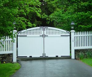Trellis and solid panel composite driveway gate with white picket fence by Tri State Gate, New York