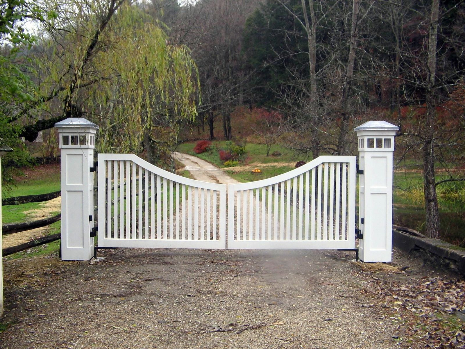 Wooden driveway gate with lighting on posts
