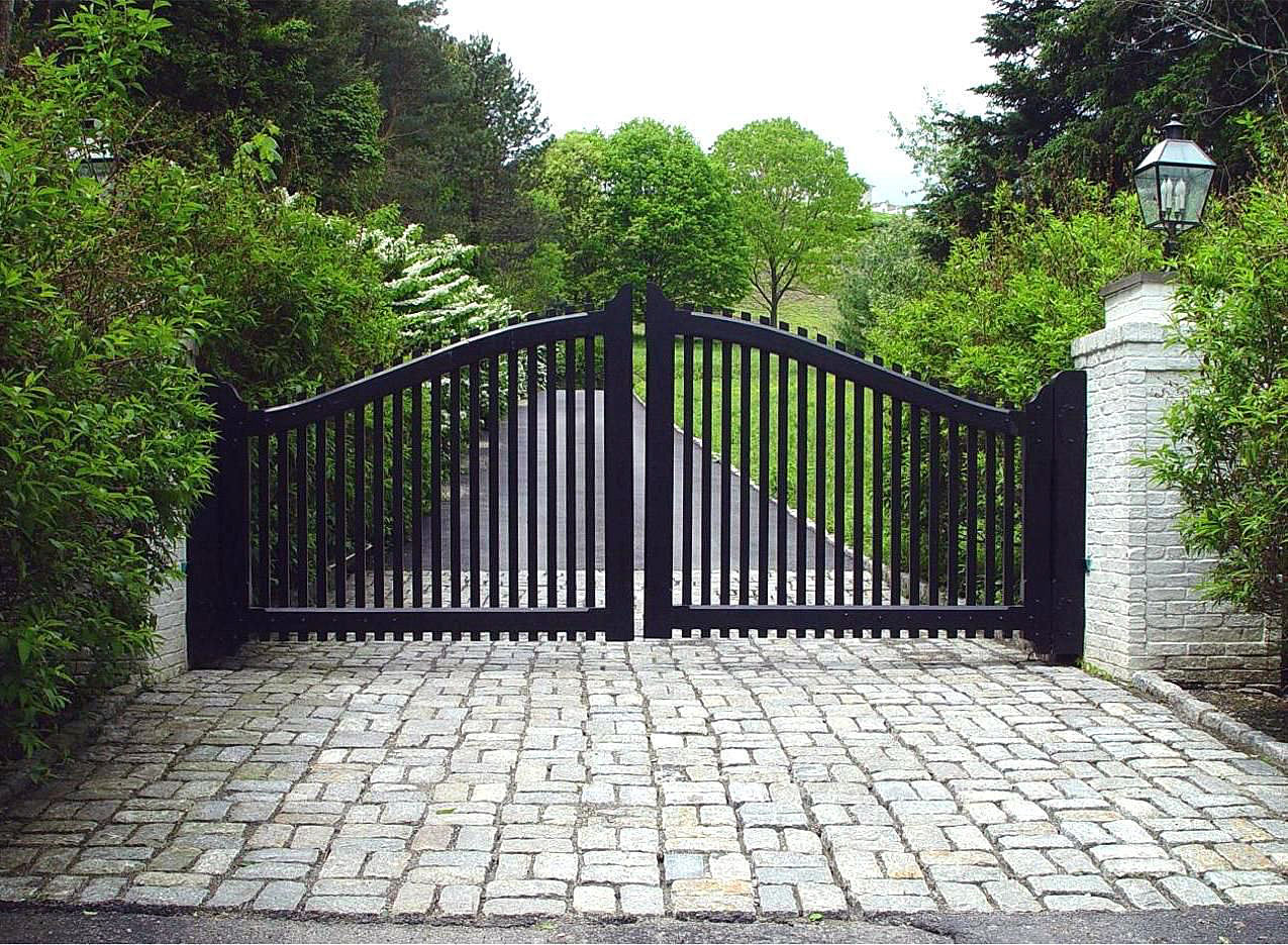 Black Wooden Swing Gates With Contrasting White Brick Pillars