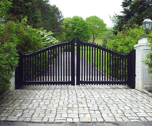 Black wooden swing gates with white brick pillars by Tri State Gate, New York