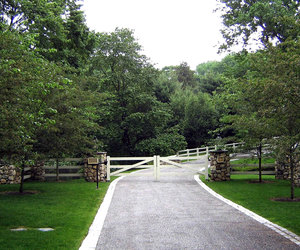 Clean, ranch-style automated gate with stone pillars by Tri State Gate, New York