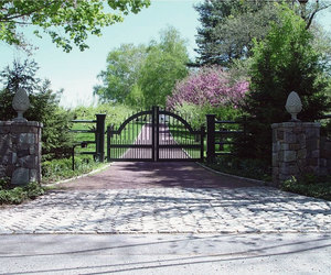 Arched wooden entrance gate with stone posts and statuary by Tri State Gate, New York