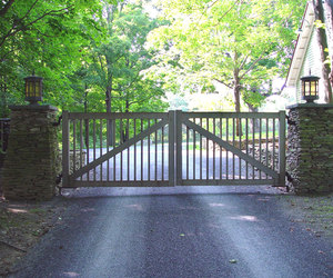 A simple weathered wood automated driveway gate by Tri State Gate, New York
