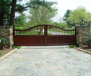 Custom-designed mahogany wood entry gate with natural stone pillars by Tri State Gate, New York