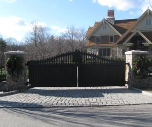 Solid wood driveway gate with picket detail on top, by Tri State Gate, New York