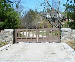 Painted composite automatic driveway gate with stone posts and wall - by Tri State Gate, New York