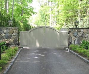 Solid panel composite driveway gate with stone walls by Tri State Gate, New York