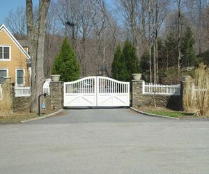 Traditional white wood driveway gate with secure entry system and white picket fencing, by Tri State Gate, New York