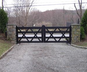 Wood driveway gate painted black with welded wire fencing added, by Tri State Gate, New York