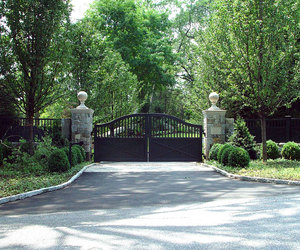 Ranch driveway gate with stone-wrapped pillars and statues, by Tri State Gate, New York