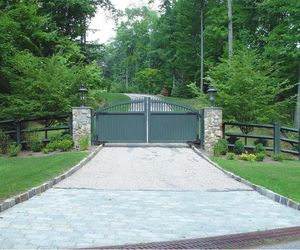 Composite driveway gate painted forest green to match post-and-rail fencing by Tri State Gate, New York