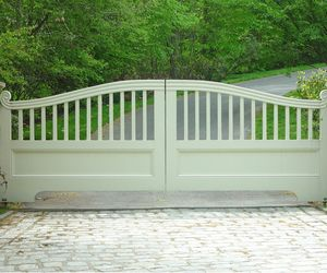 Traditional wooden driveway gate with custom scroll detail by Tri State Gate, New York